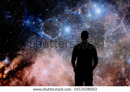 Young man standing in front of the huge picture of star nebula. Man in the universe. Man watching the space. Meaning of life. Visiting the observatory. Elements of the image furnished by NASA.  Foto stock ©