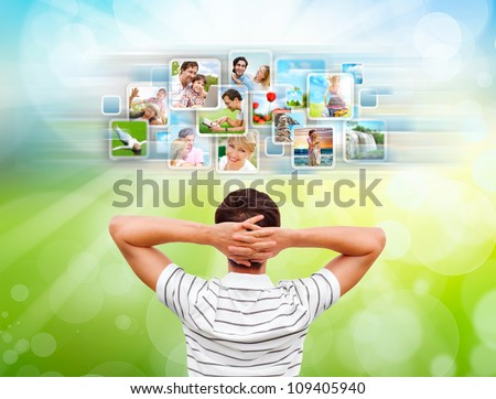 Young man standing in front of virtual preview of different images and choosing channel