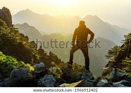 Young man standing in the summer mountains at sunrise and enjoying view of nature.