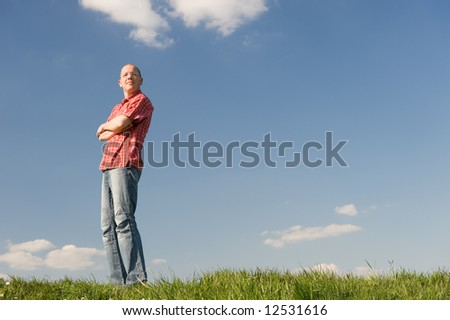 Young man standing on a meadow with a look into the future
