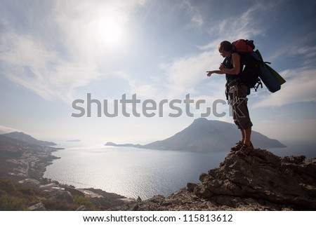 Young man standing on a rock against picturesque view of sea