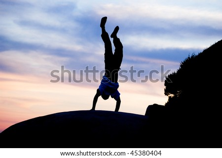 young man standing on arms on the stone on sunset