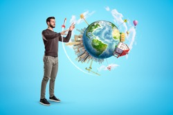 Young man standing on light blue background trying to touch small Earth which is floating in air, with big city, house and road signs on it. Global thinking. Optimistic perspectives.