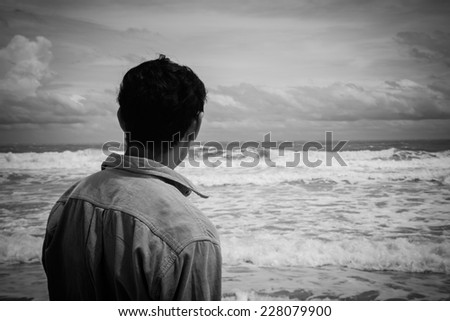 Young man standing on the beach looking to sea  ,Black and white