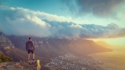 Young man standing on the edge at the top of Lion's head mountain in Cape Town with a beautiful sunset view