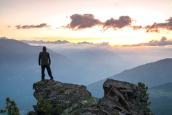 Young Man Standing on the edge of a cliff and enjoys the sunrise in southtyrol Italy
