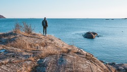 Young man standing on the rock by the sea in sunny , winy day and looking on the horizon far away