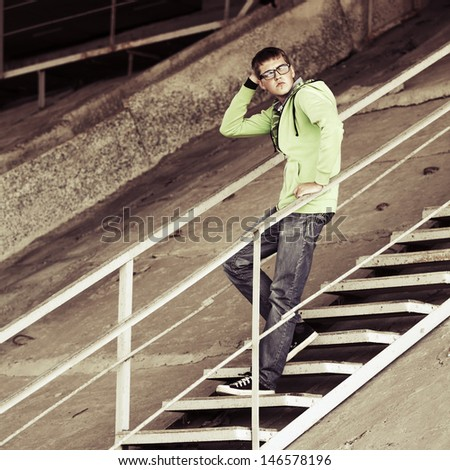 Young man standing on the steps - stock photo