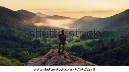 Young man standing on top of cliff in summer mountains at sunset and enjoying view of nature