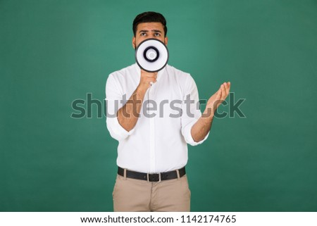 Young man standing puts the megaphone on the front of his mouth shows only his eyes talking to the audience looking up with eyes on green background.