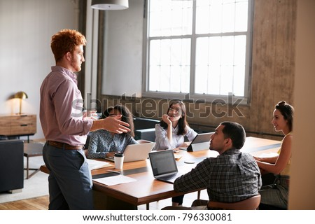 Young man standing to address colleagues at a work meeting