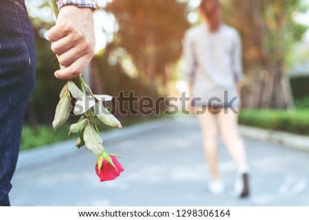 young man standing with a Red Rose on Hand Sadness Love in Ending Break up of Relationship Blurred woman Back Side Walking away parting  in public park outdoor.  Broken Heart in Valentine day Concept.