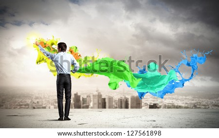 young man standing with back painting splashes against city background
