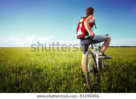 Young man standing with bicycle on a green grass and looking to the horizon