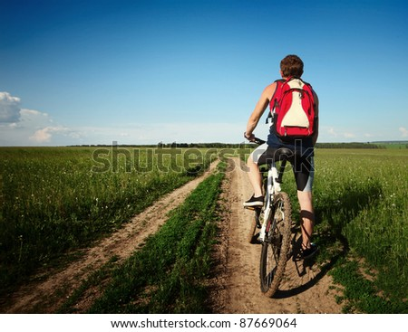 Young man standing with bicycle on an countryside road