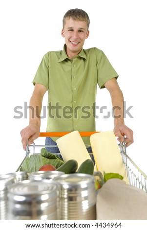 Young man standing with full of things trolley. Smiling and looking at camera. Front view - stock photo