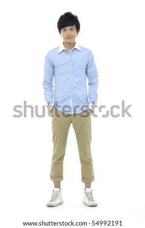 Young man standing with hands in pockets