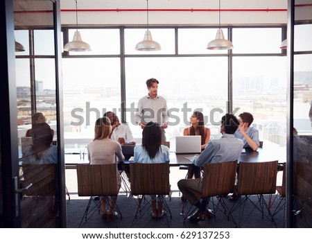 Young man stands addressing team at a meeting in a boardroom