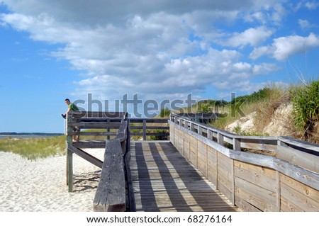 Young man stands barefoot on a weathered dock on the beach at Cape Charles, Virginia.  A bank of clouds forms overhead and vivid blue fills the skies.