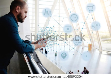 Young man stands in airport interior and checking online schedule of flights through mobile phone application. Hipster guy surfing network, connecting with people and shopping. Infographics symbols - Shutterstock ID 1145893304