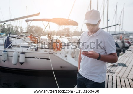 Young man stands on pier. He holds phone in hands and look at it. There are yachts behind him from one side of pier.