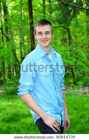 Young man stands surrounded by green forest.  He is wearing a light blue button front shirt and jeans.