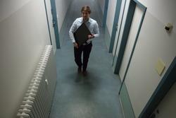 Young Man Stealing Computer Monitor Walking In Building Corridor
