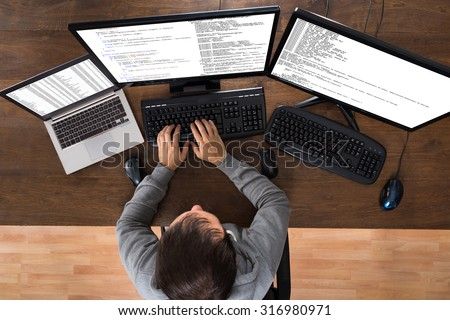 Young Man Stealing Data From Computers And Laptop At Desk