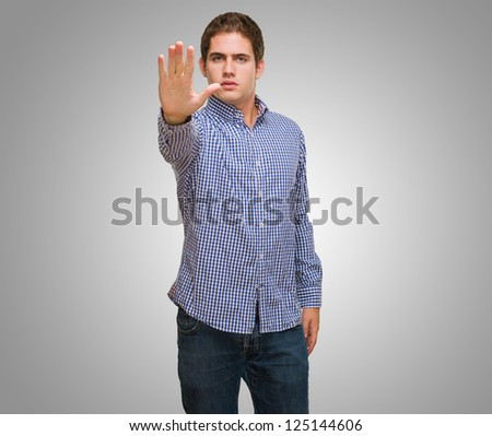 Young Man Stopping With Hand against a grey background