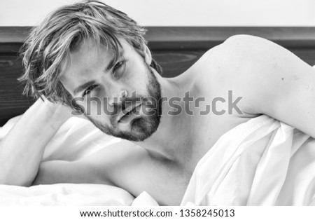 Young man stretching while waking up in the morning. Picture showing young man stretching in bed. Wake up morning