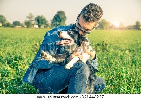 Young man stroking his playful dog - Cool dog and young man having fun in a park - Concepts of friendship,pets,togetherness