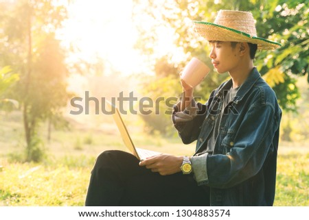 Young man student using laptop outdoor in the field drinking coffee in the morning. Young man student studying, drinking coffee in the morning in relaxation pose. Education and life style concept. #1304883574