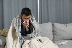 Young man suffering from a common cold and flu or allergy sit at home wrapped in blanket and wipe his nose with tissues while he have a strong headache pain, healthcare concept