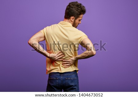 young man suffering from backache. close up back view photo. studio shot.disk herniation, slipped disk