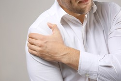 Young man suffering from pain in shoulder, closeup