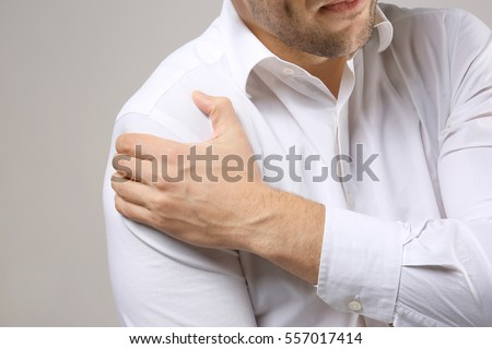 Young man suffering from pain in shoulder, closeup #557017414