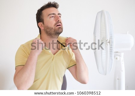 Young man suffering from summer heat and high humidity level