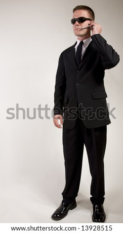 Young man suggesting a secret service agent or secret  policeman listening on a headset.