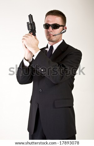 Young man suggesting a secret service agent or secret policeman with armed a gun.