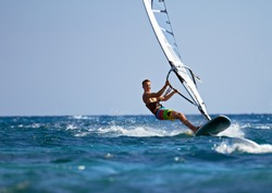 Young man surfing the wind on a bright summer day