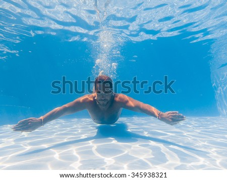 Young man swimming underwater in the swimming poll #345938321