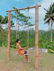 Young man swinging and relaxing  in the jungle rainforest of Bali island, Indonesia. Swing in the tropics.