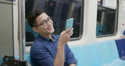young man take train or MRT and use the phone