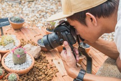 Young man takes a photo with DSLR camera + 35mm lens. Enthusiastic Asian photographer shoots a blooming plant (cactus) from short distance. Suan Luang King Rama 9 Park (Bangkok).