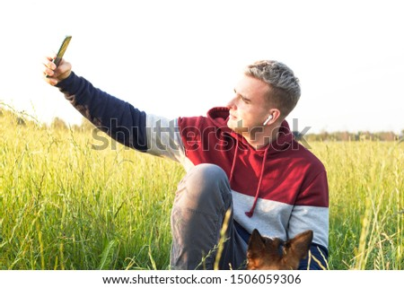 Young man takes a selfie in a field in a meadow. A handsome guy photographs himself outdoors or outdoors. A person at sunset is holding a mobile phone.