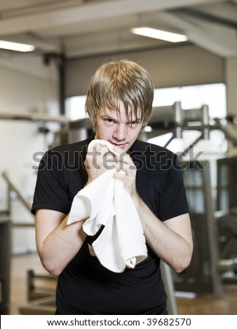 Young man taking a break from training at a fitness center