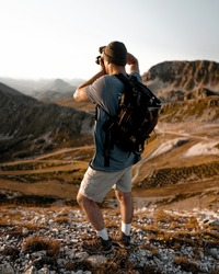 young man taking a photograph of sunrise on top of a mountain, unmarked clothing with backpack hat and trekking boots