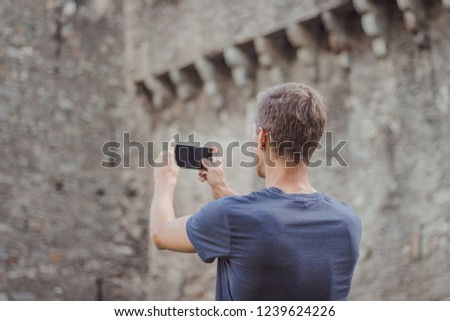 Young man taking a picture with a phone during the day. Subiect old castle drawbridge.