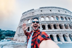 Young man taking a selfie in front of Colosseum in Rome, Italy - Happy tourist visiting Coliseum in Rome