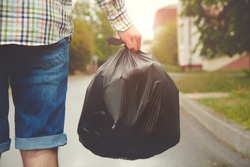 young man taking out garbage in black plastic bag